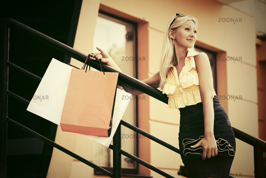 Happy young fashion woman with shopping bags against a mall window