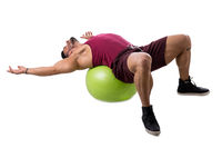Muscleman exercising abs on an exercise ball