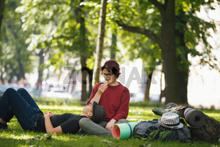 Couple of teenagers tourists with backpacks have rest in the city park