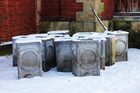 few concrete gray garbage urns stand in a park in the snow.