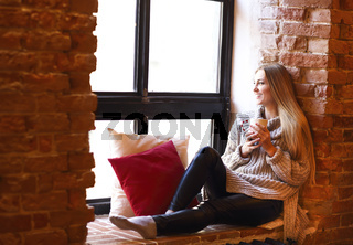 Young pretty girl with cup sitting near window