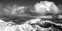 Panoramic view on snowy ridges in sun winter day