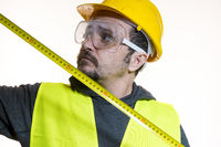 taking measurements with a meter, a man who wants to do a work without knowledge, work without experience. Do it yourself, man dressed in yellow builder helmet with protective glasses ready to start the construction work