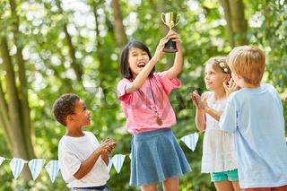 Asiatisches Mädchen freut sich über Pokal