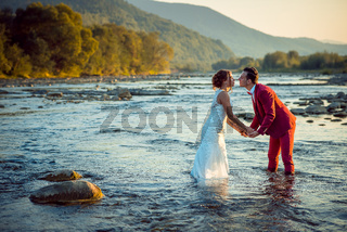 Romantic outdoor portrait of the beautiful newlyweds holding hands and going to kiss while standing in the water during the sunset.