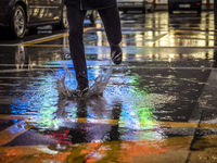 Crop man stepping in puddle on street