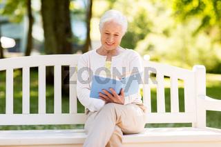 happy senior woman reading book at summer park