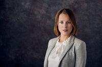 Elegant woman standing against dark background