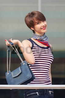Happy young fashion woman with handbag next to mall windows