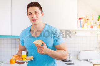 Frühstück essen Mann jung in der Küche morgens Morgen Textfreiraum