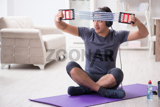 Man doing sports with resistance band and listening to music