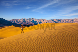 Woman in striped shirt  photographing sand waves