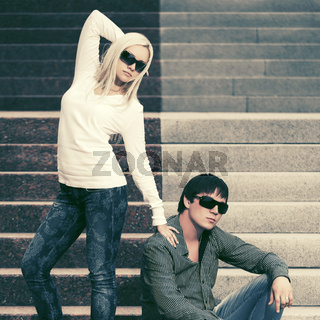 Young fashion couple in sunglasses on the steps