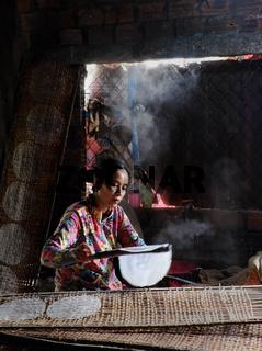 Vietnamese woman making rice paper