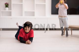 boys having fun with an apple on the floor