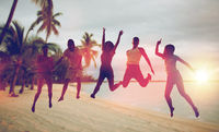 happy friends dancing and jumping on beach