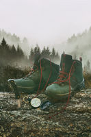 Hiking boots with knife and compass on tree log