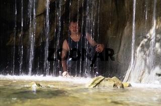 Mann hinter Wasserfall