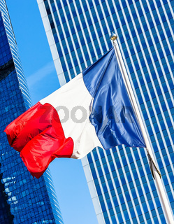 French flag with business building on background