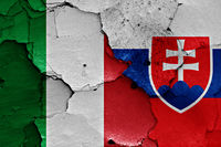 flags of Italy and Slovakia painted on cracked wall