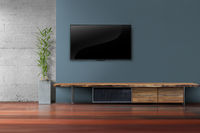 Living room led tv on dark blue wall with wooden table