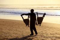 Peanut seller on the beach at sunset