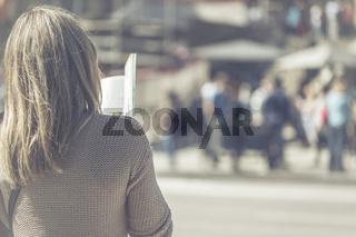 Eine Frau steht mit dem Rücken zur Kamera und liest einen Reiseführer.
