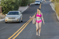 Blonde Model Hitchhiking Down A Highway