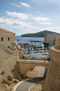 Port and tourists viewed through fortress walls in Dubrovnik, Croatia
