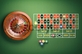 Casino roulette wheel with casino chips on green table. Gambling background.