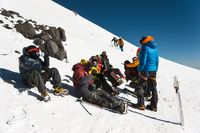 fully equipped Professional mountaineers on a stop sit on a snowy slope in sunny weather.