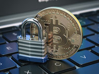 Cryptocurrency bitcoin coin and padlock lock on computer keyboard. Internet security and protection concept.
