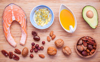 Selection food sources of omega 3 and unsaturated fats. Superfood high vitamin e for healthy food. Almond ,pecan ,hazelnuts,walnuts ,olive oil ,fish oil ,avocado and salmon on bamboo cutting board.