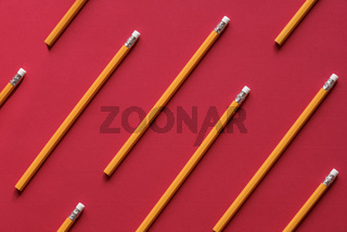 Yellow wooden pencil on red background