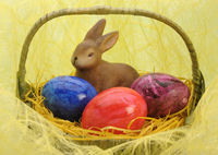 bunny and three painted eggs in easter nest