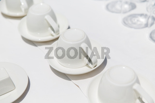 white coffee cups upside down on saucers