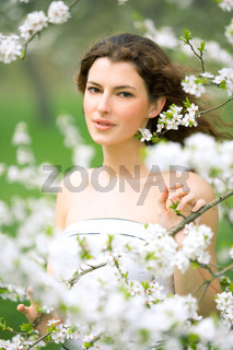 portrait of young brunette in the spring garden