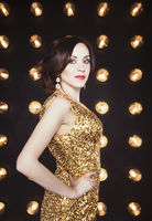 Superstar woman wearing golden shining dress posing