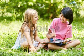 Zwei Mädchen malen zusammen ein Bild mit Kreide