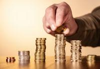 Eine Münze wird auf einen Stapel mit Münzen gelegt