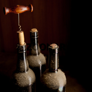 Three old wine bottles and corkscrew