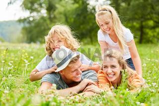 Familie und Kinder lachen im Gras