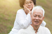 Old Asian couple smiling outdoor.