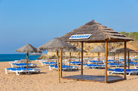 Many wicker parasols and beach beds