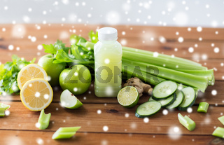 bottle with green juice, fruits and vegetables