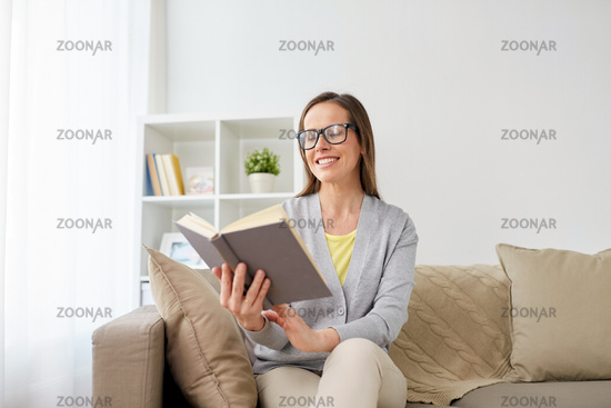 happy woman in glasses reading book at home