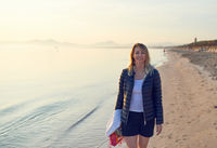Blond smiling woman walking along beach