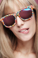 Closeup portrait of young blonde female with fun candy glasses bites his lip
