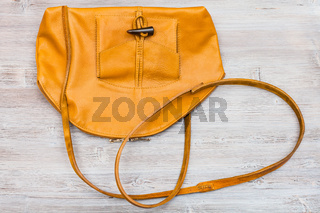 yellow leather bag on wooden table