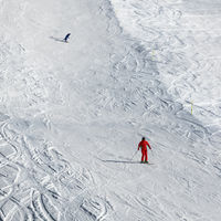 Skier and snowboarder downhill on snowy ski slope at sun winter day